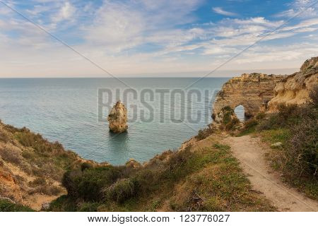 Trail of the Arch on the beach Marinha, Portugal. The waves on the shore.