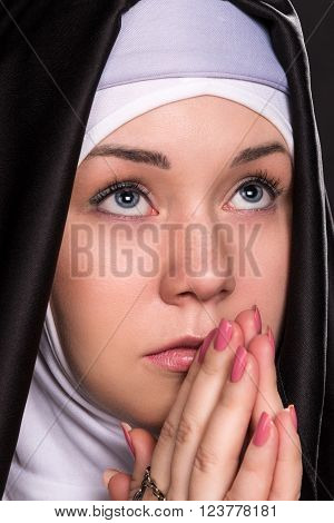 Portrait of praying nun who looks up close up face only