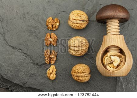 Healthy food - nuts. Walnut kernels and whole walnuts on slate. Walnuts and wooden nutcracker. We like walnuts. Advertising on walnuts.