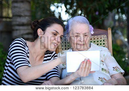Girl Show Tablet To Grandma