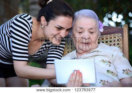 Girl And Grandma Hold Tablet