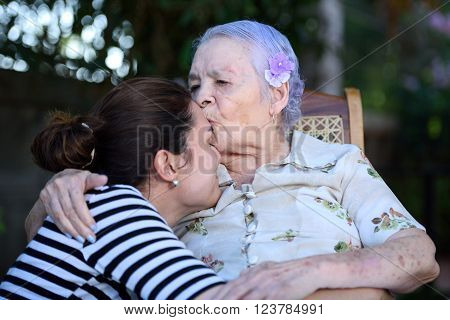 Happy grandma kissing her granddaughter in park