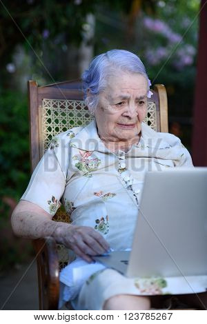 Grandma using and talking on a laptop