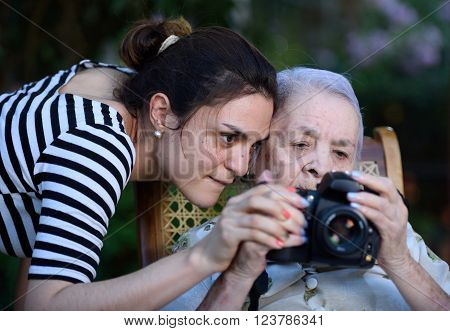 grandma browsing photos on DSLR camera with young girl