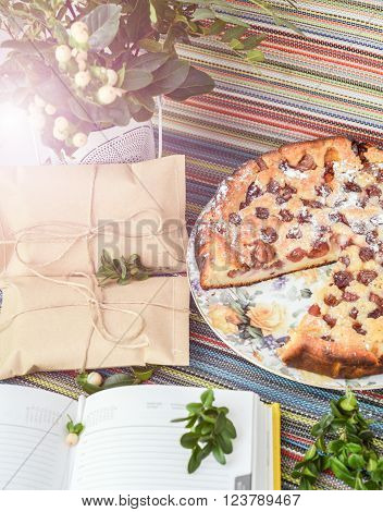 notepad paper envelope and piece of pie on the colorful tablecloth. sunlight