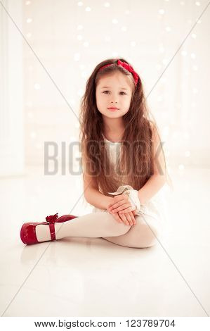 Cute kid girl 5-6 year old wearing stylish clothes sitting on floor in room over white. Looking at camera. Childhood.