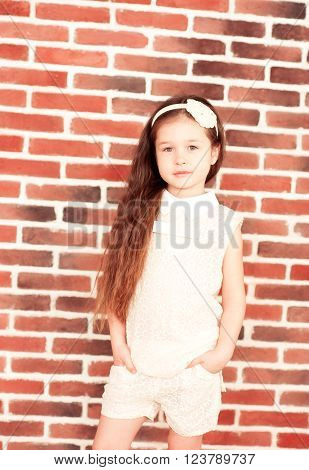 Smiling baby girl 5-6 year old wearing stylish clothes in room over brick wall looking at camera. Childhood.