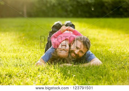 Devoted father and daughter lying on grass, enjoying eachothers company, bonding, playing, having fun in nature on a bright, sunny day. Parenthood, lifestyle, childhood and family life concept.