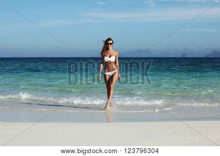 Beautiful fit woman in bikni walking from sea to tropical beach