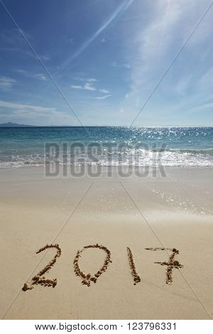 Drawing 2017 on the sand of a tropical beach
