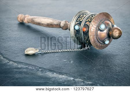 Vintage toned old Tibetan prayer wheel used to accumulate wisdom and good karma and to purify bad karma, shallow depth of field.