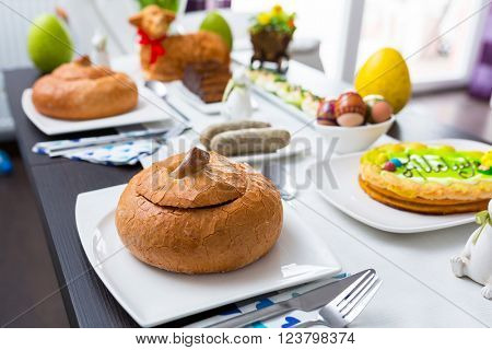 Easter traditional polish breakfast with white borsch soup in bread bowl, eggs and white sausages