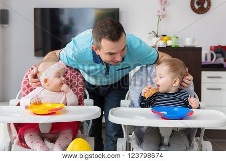 Father with baby boy and girl twins eating lunch on the high chair.