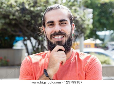 Happy guy with beard looking at camera outside in the city
