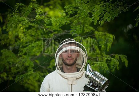 beekeeper in a protective suit with smoke tool
