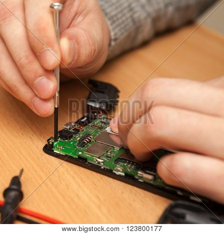 Repairer To Disassemble The Smartphone. Hands Close-up.