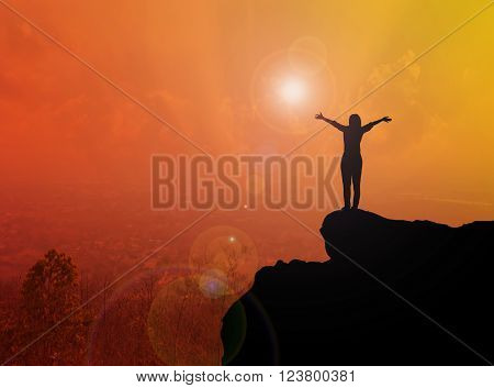Women silhouette standing on cliff with blurred city top view and sunlight effect with copy space