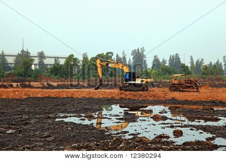 reflection of Excavator Loader with backhoe standing in sandpit