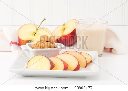Health snack of fresh red apple and peanut butter with a glass of milk.