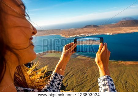 Woman photographing with smart phone Graciosa island from El Rio viewpoint on Lanzarote island in Spain