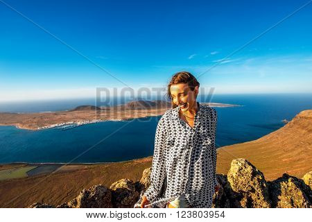 Female tourist standing on El Rio viewpoint on Lanzarote island with Graciosa island on the background in Spain
