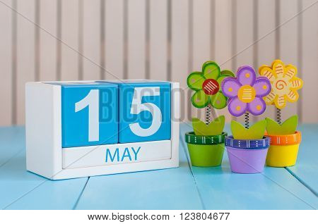 May 15th. Image of may 15 wooden color calendar on white background with flowers. Spring day, empty space for text. World Remembrance Day Of AIDS Victims.