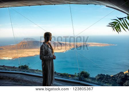 Woman looking on Graciosa island from El Rio viewpoint on Lanzarote island in Spain