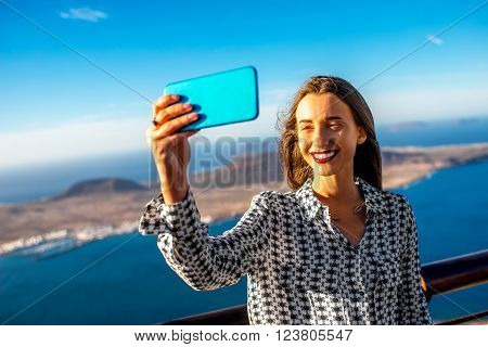 Woman making selfie photo with great view on Graciosa island standing on El Rio viewpoint on Lanzarote island in Spain