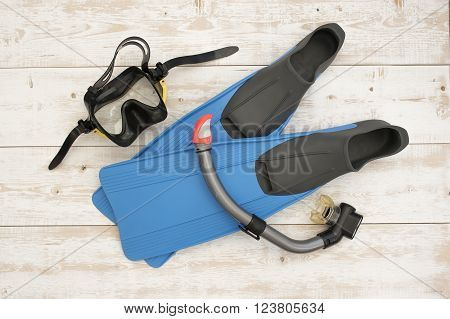 Fins, mask and snorkel diving on a wooden background