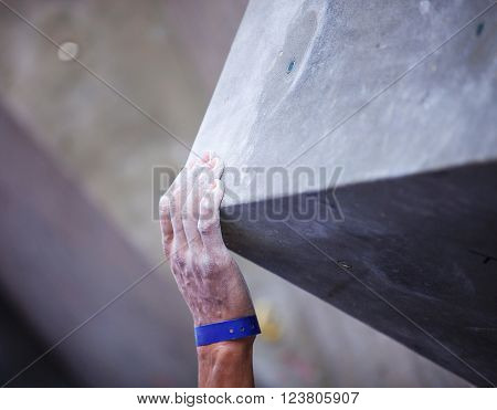 Closeup of man's hand on handhold on artificial climbing wall, hand in focus