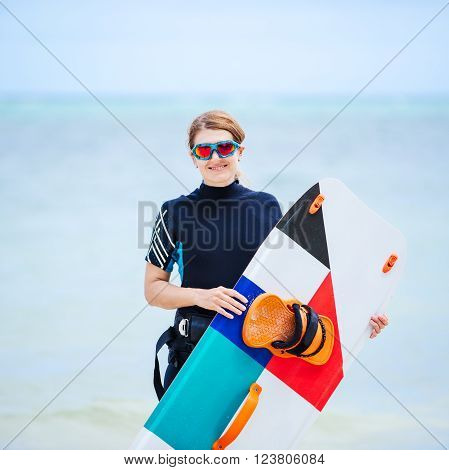 Wakeborder girl at the tropical beach with her surfboard