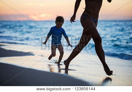 Mother and son having fun on beach at sunset, running along water's edge
