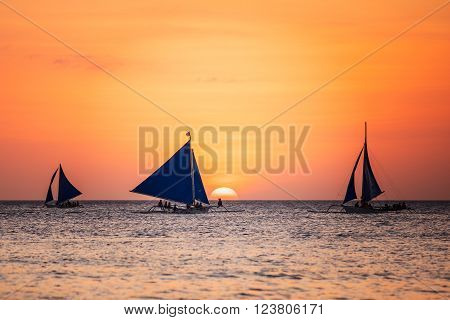 Sunset seascape with a sailboat. Boracay island, Philippines