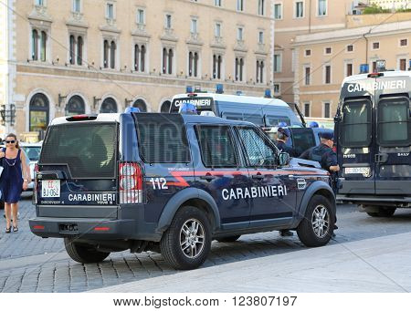 Rome, Italy - June 25, 2014: Police stand near a police car on one of the main streets of Rome during a public event.