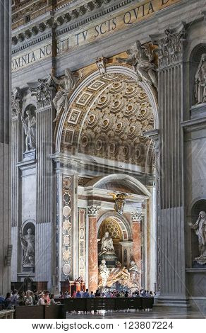 Vatican Italy - June 26 2014: People at the interior of the Saint Peter Cathedral in Vatican. Saint Peter's Basilica has the largest interior of any Christian church in the world.
