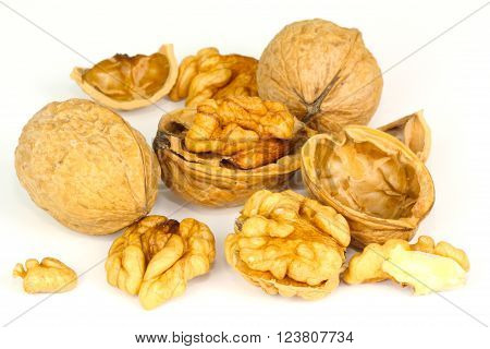 some walnuts broken against a white background