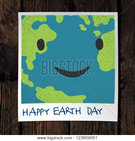 Photo frame with Earth snapshot closeup. Earth day concept. On wooden background.