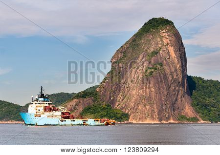 RIO DE JANEIRO, BRAZIL - FEBRUARY 26, 2016: Maersk Launcher in Guanabara bay passing the Sugarloaf Mountain. Launcher is an anchor handling supply tug vessel.