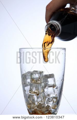 pouring cola drink to glass with ice