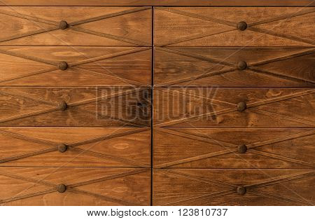 Closeup amazing gorgeous front view of old vintage, retro classic wooden drawer dresser with wooden Knobs background