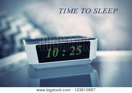 Digital clock showing 10:25 o'clock on a bedside table in bedroom