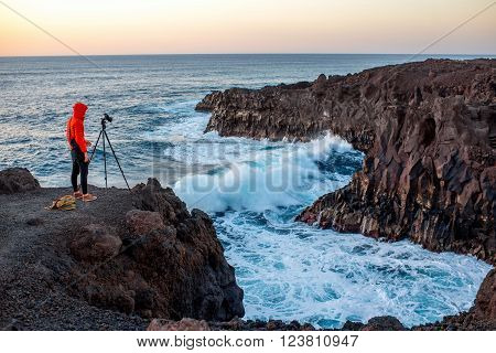 Man photographing with tripod beautiful rocky coast with wavy ocean on the sunset on Lanzarote island in Spain