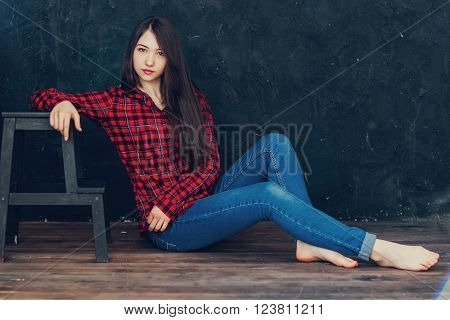 beautiful girl sitting near the ladder in the Studio
