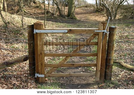 Small and narrow five bar wooden gate with wire fencing either side in an open woodland setting.