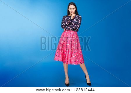 Full length portrait of a charming woman in colourful dress showing finger over lips on blue background