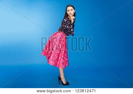 Full length portrait of a beautiful woman showing finger over lips on blue background