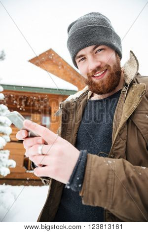 Cheerful attractive bearded man using mobile phone standing in front of log cabine in winter