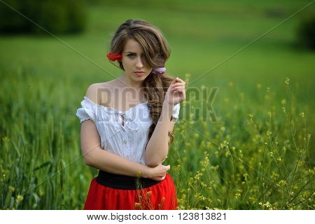 young beautiful woman on cereal field with poppies in summer sunny day