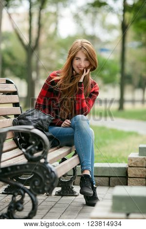 Young laughing redhead woman in red plaid jacket and blue jeans sitting on park bench with blurred park background