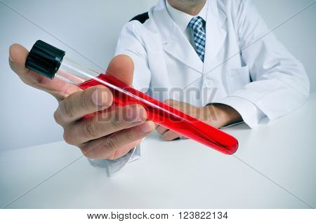 closeup of a young caucasian man wearing white coat sitting at his desk holds a blood sample in his hand
